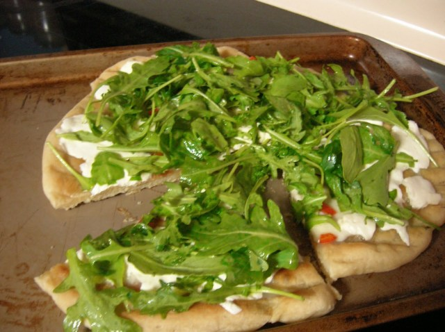 The hot pizza is topped with lightly dressed greens and is ready to serve!